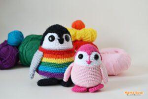 Laponio el pingüino amigurumi, que he vestido con un chaleco con los colores del Orgullo, junto con la versión rosa y más pequeña del pingüino.